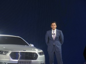 Ford Motor Company Chief Executive Officer Mark Fields standing next to the China-exclusive Ford Taurus.