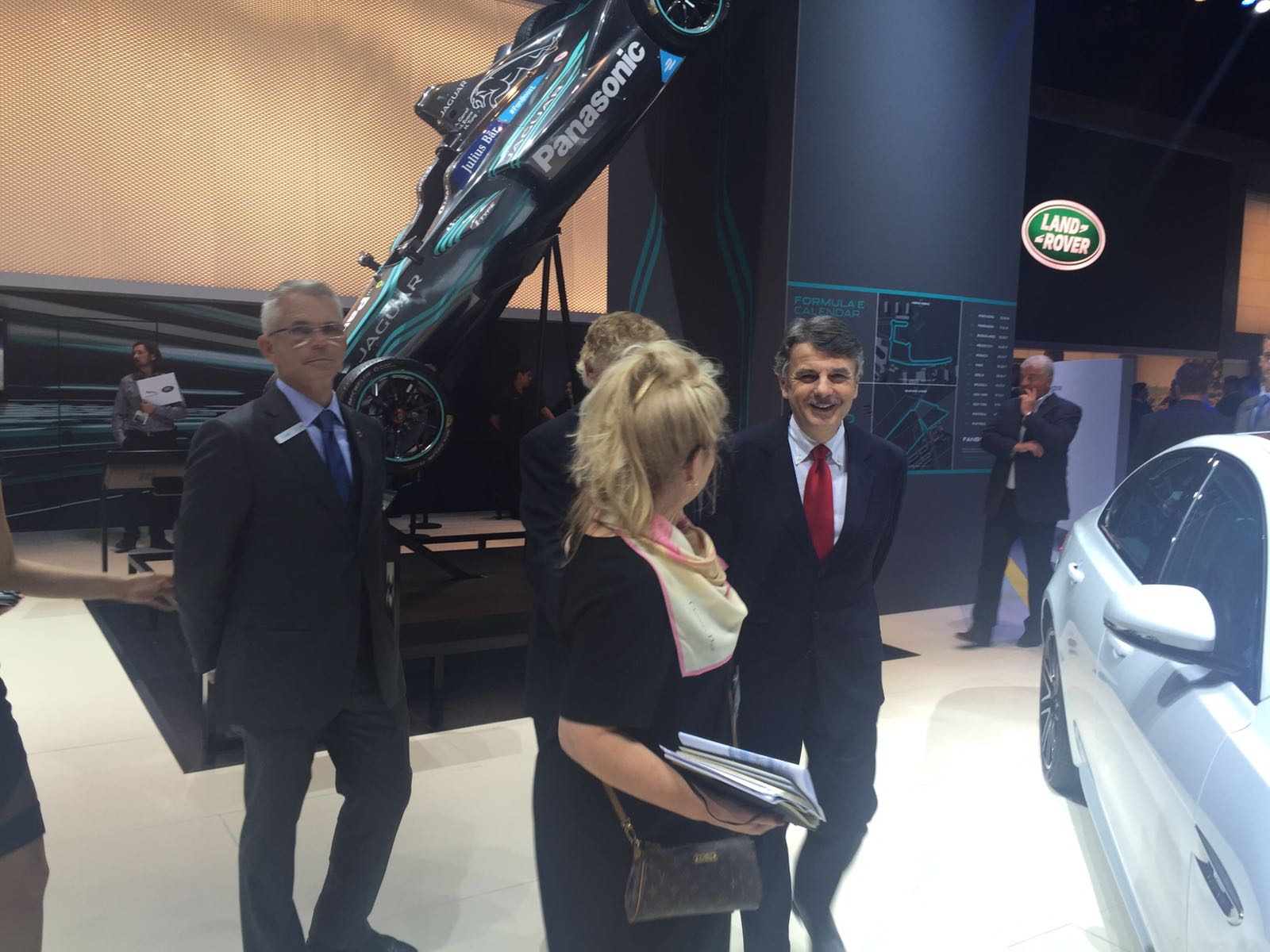Jaguar Land Rover CEO Ralf Speth walks in front of Jaguar Racing's formula-E vehicle with LIASE Group Non-Executive Board Member Vic H. Doolan (hidden).